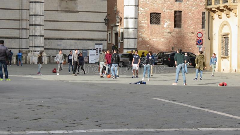 Italian schoolboys and schoolgirls in a schooltrip playing foot in the Cathedral square stock photos