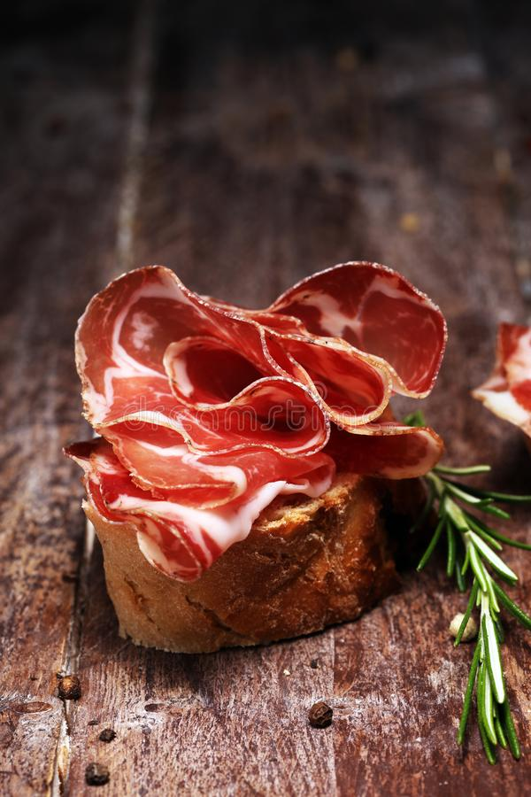 Italian sliced cured coppa with spices. Raw ham. Crudo or jamon with rosemary. Italian sliced cured coppa with spices. Raw ham. Crudo or jamon on wood royalty free stock image
