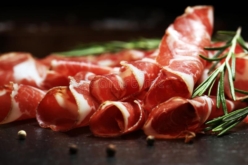 Italian sliced cured coppa with spices. Raw ham. Crudo or jamon with rosemary. Italian sliced cured coppa with spices. Raw ham. Crudo or jamon on wood royalty free stock photography