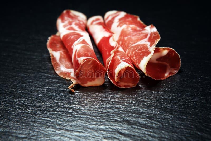 Italian sliced cured coppa with spices. Raw ham. Crudo or jamon with rosemary. Italian sliced cured coppa with spices. Raw ham. Crudo or jamon on wood stock photos