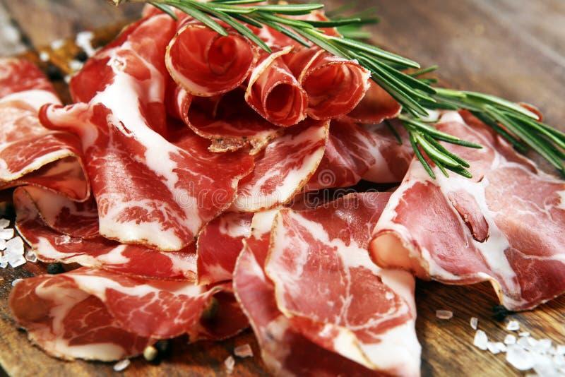 Italian sliced cured coppa with spices. Raw ham. Crudo or jamon with rosemary. Italian sliced cured coppa with spices. Raw ham. Crudo or jamon on wood royalty free stock photo