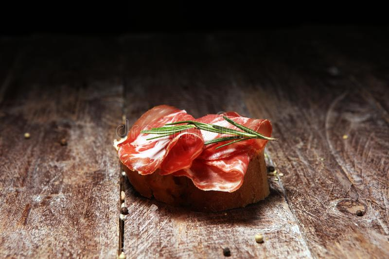 Italian sliced cured coppa with spices. Raw ham. Crudo or jamon with rosemary. Italian sliced cured coppa with spices. Raw ham. Crudo or jamon on wood stock photography