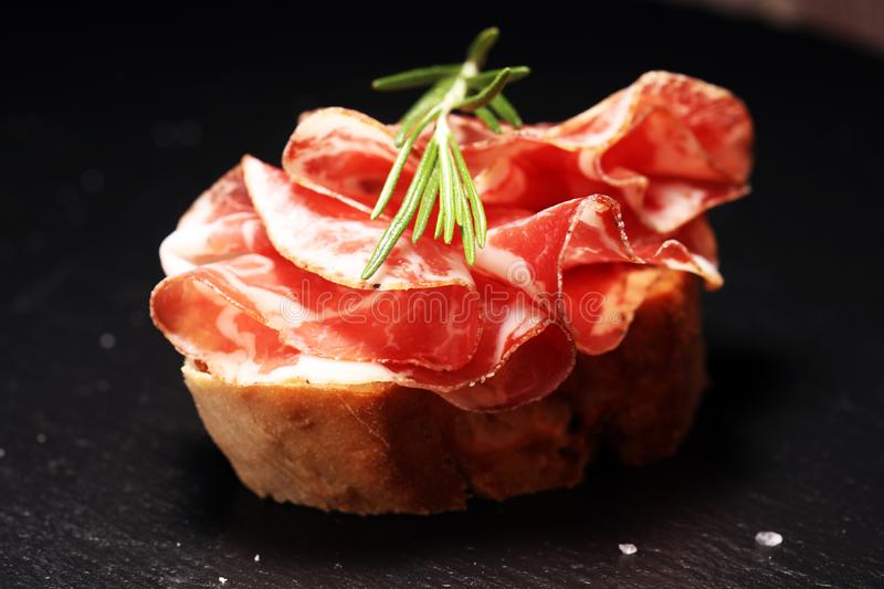 Italian sliced cured coppa with spices. Raw ham. Crudo or jamon with rosemary. Italian sliced cured coppa with spices. Raw ham. Crudo or jamon on wood stock images