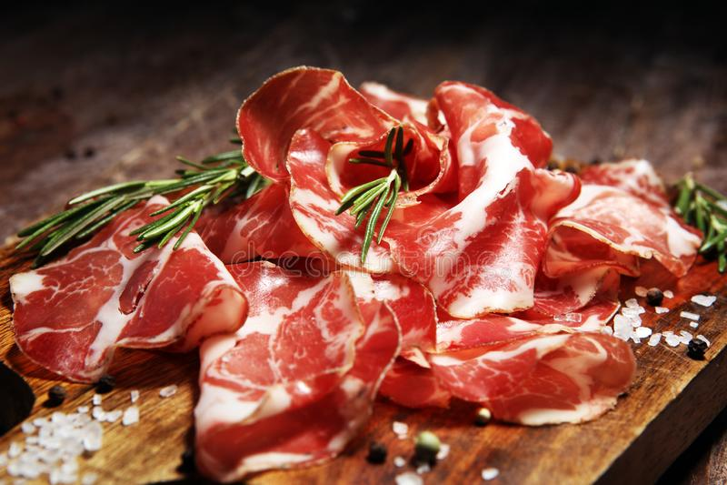 Italian sliced cured coppa with spices. Raw ham. Crudo or jamon with rosemary. Italian sliced cured coppa with spices. Raw ham. Crudo or jamon on wood stock photo