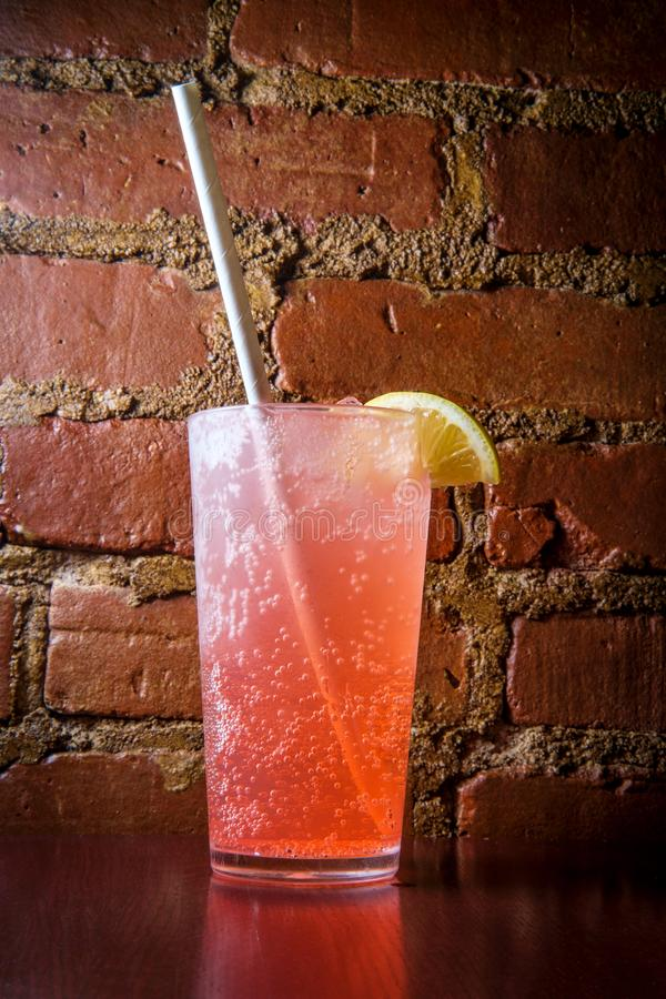 Italian Soda Paper Straw. Pink Italian soda pop beverage with ice and biodegradeable paper straw stock images
