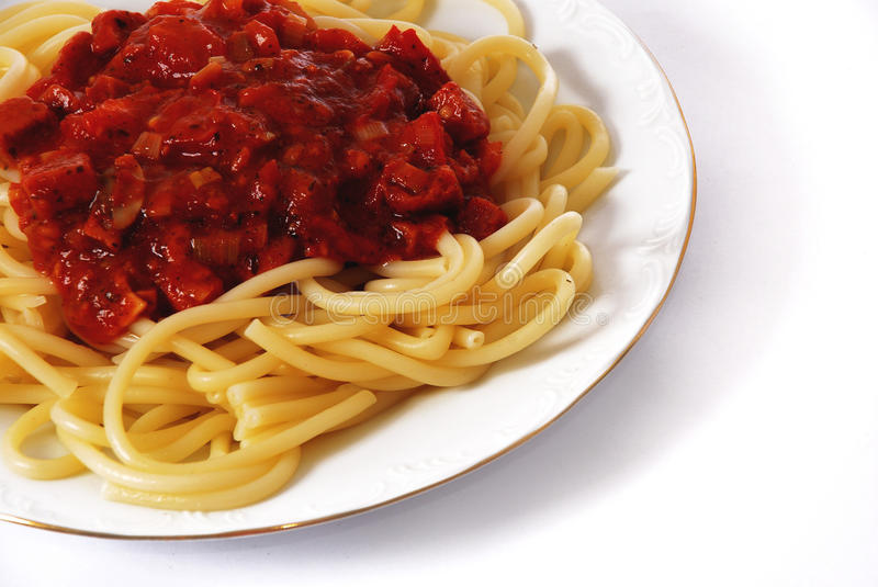 Italian spagetti. Cooked in a white plate isolated on white royalty free stock image