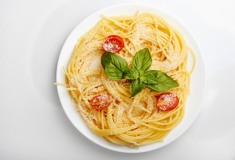 Italian spaghetti with cherry tomatoes, basil and parmesan on a white plate. View from above royalty free stock photography