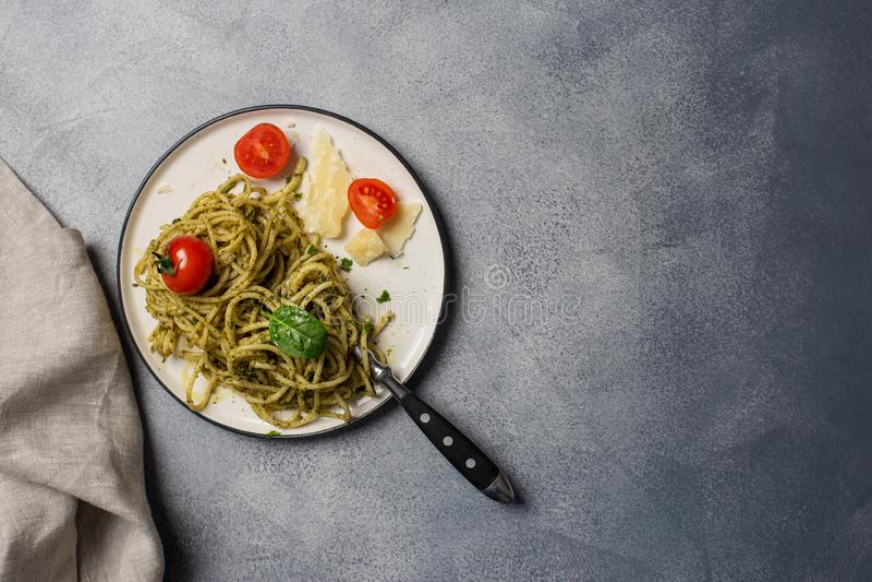 Italian spaghetti with pesto, herbs and cherry tomatoes at white plate stock photos