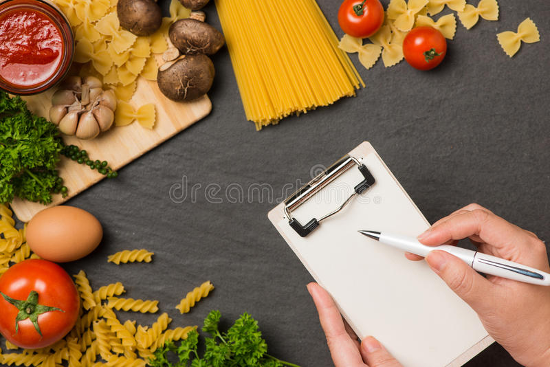 Italian spaghetti photo recipe. Hand with pen writting on blank stock photo