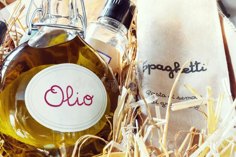 Italian specialty gift pack. Age with olive-oil and spaghetti on straw royalty free stock images
