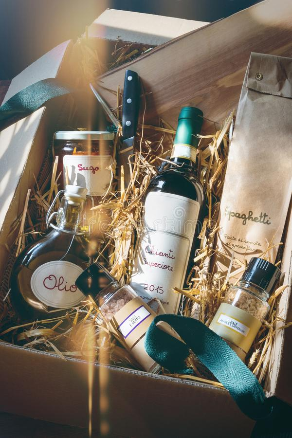 Italian specialty gift pack. Age with red wine, spaghetti, oil, tomato sugo and spice-salt on straw, light reflex stock image