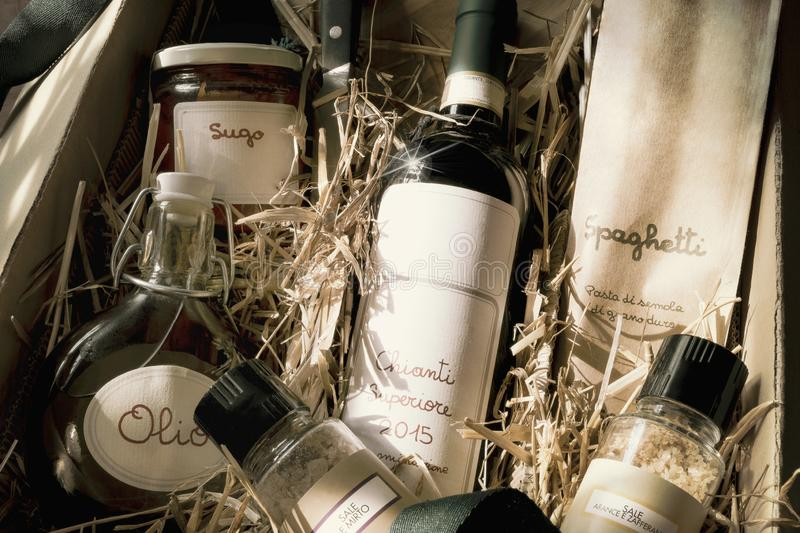 Italian specialty gift pack. Age with red wine, spaghetti, oil, tomato sugo and spice-salt on straw, vintage royalty free stock image