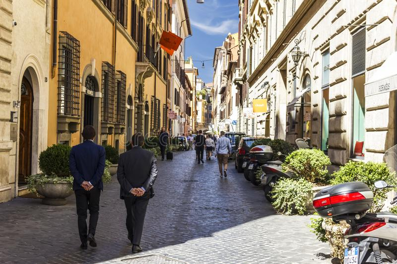 Rome/Italy - August 27, 2018: Busy Roman Street with Fashionable City People, Boutiques and Motor Scooters parking royalty free stock images
