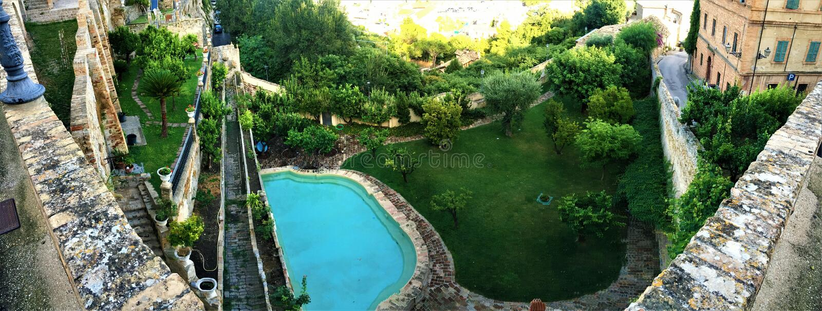 Garden with pool, trees and historical buildings. Italian style, Grottammare, Marche, view, landscape, sunny sky, garden with pool, trees and historical royalty free stock images