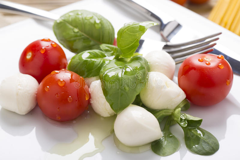 Italian style mozzarella, salad and basil royalty free stock photography