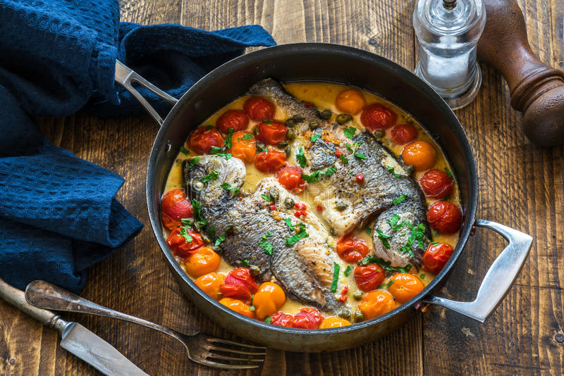 Italian style sea bream in crazy water - acqua pazza. On wooden table royalty free stock images