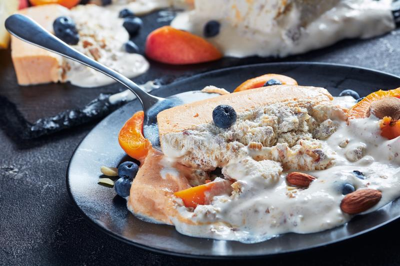 Italian summer dessert, a portion of melted Sicilian Almond apricot melon Semifreddo served on a black plate with fruits and berri. Es, view from above, close-up stock image