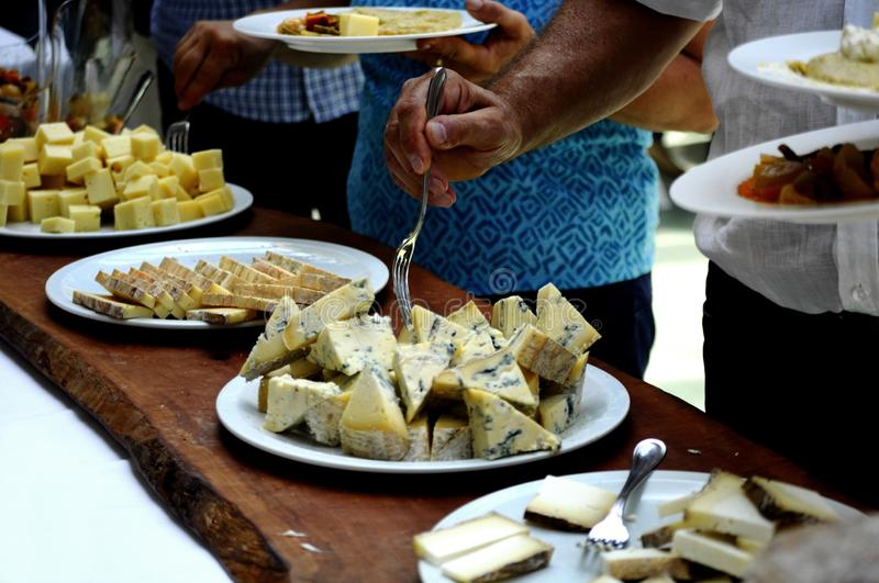 Italian Taleggio cheese tasting on a buffet table at a dinner party - delicious cheese plates on a wooden table, food for wine. Closeup on a hand taking royalty free stock images