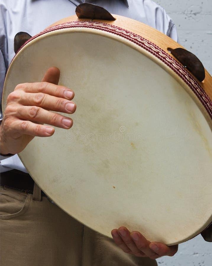 Italian tambourine. Italian musician playing tarantella with tambourine of wood, goat skin and cymbals royalty free stock photo