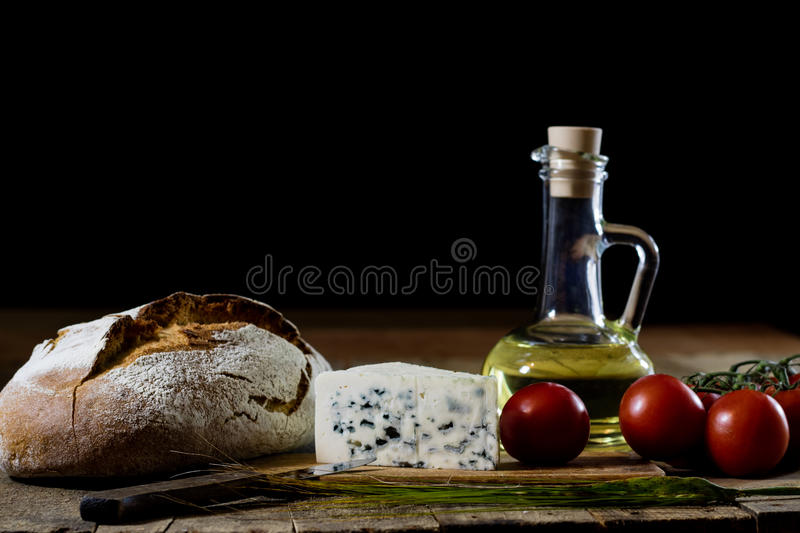 Italian tasty food, olive oil, white cheese and tomatoes. Black background royalty free stock photography