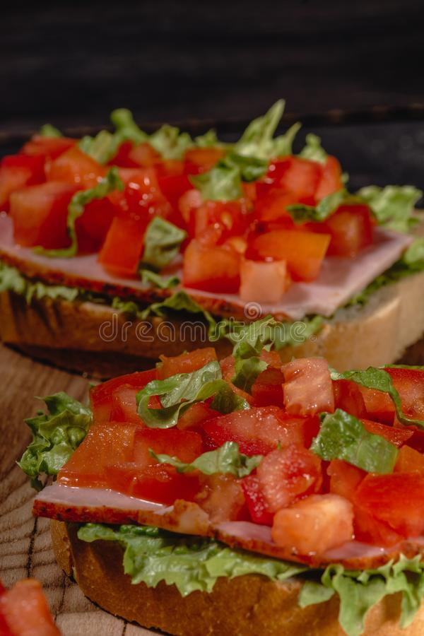 Italian tomato bruschetta with chopped vegetables, herbs and oil on grilled or toasted crusty ciabatta bread stock image
