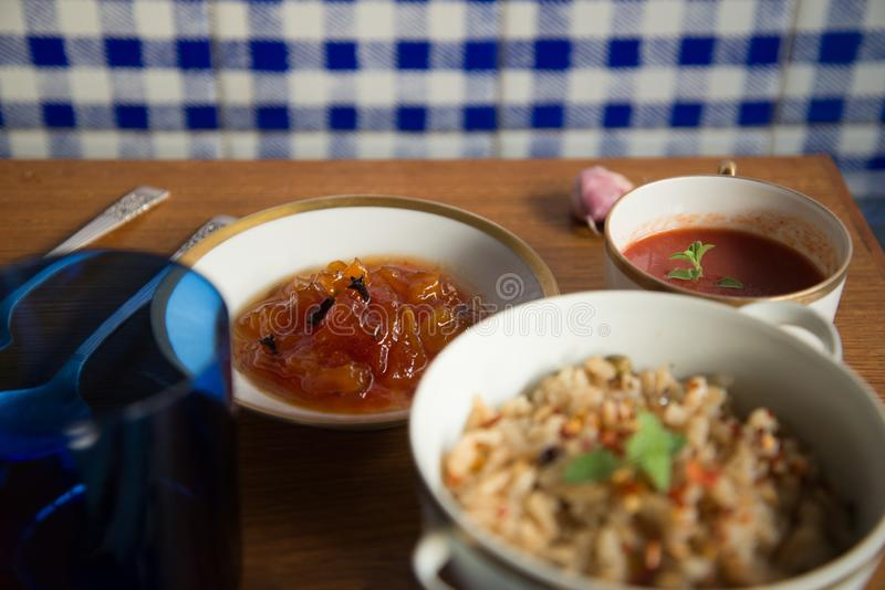 Italian tomato soup Brown rice risotto Papaya dessert served in Chinese porcelain dishes blue glass royalty free stock photos