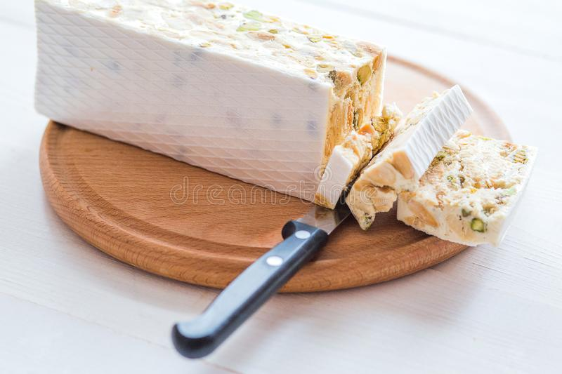 Italian torrone or nougat with almonds on a white wooden table, close up with selected focus stock image
