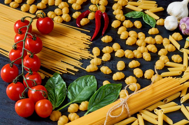 Italian traditional food, spices and ingredients for cooking as basil, cherry tomatoes, chili pepper, garlic and various pasta royalty free stock photography