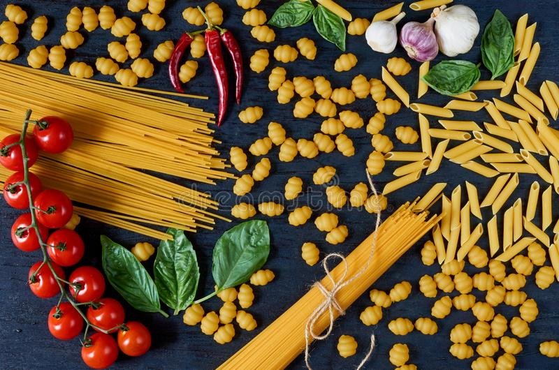 Italian traditional food, spices and ingredients for cooking as basil leaves, cherry tomatoes, chili pepper, garlic, various pasta royalty free stock images