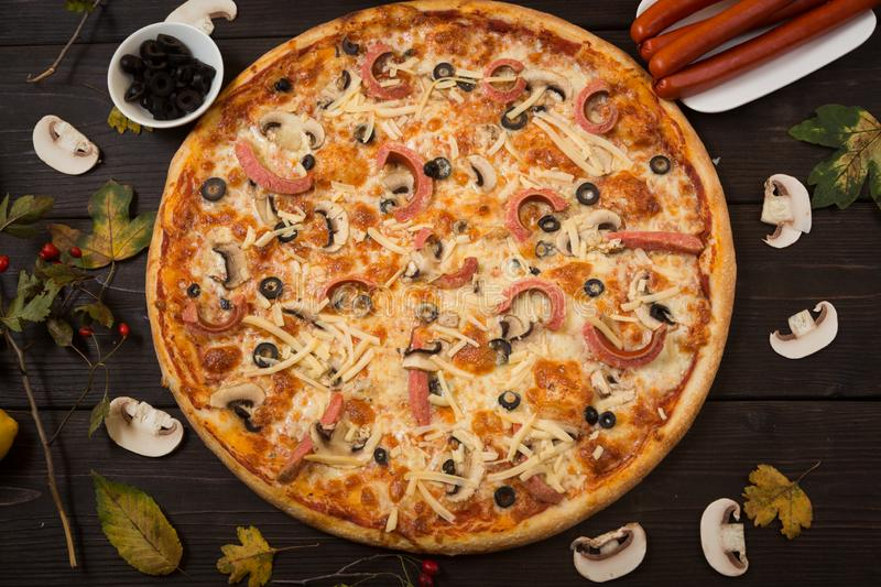 Italian traditional pizza with sausages and mushrooms stock photo
