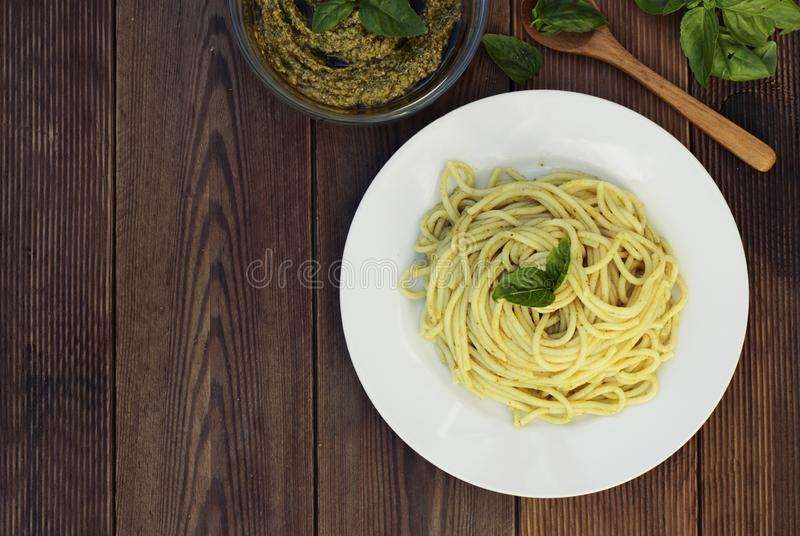 Italian traditional spaghetti with basil pesto pasta with cheese, pine nuts, olive oil, rustic table. Copy space. royalty free stock photo