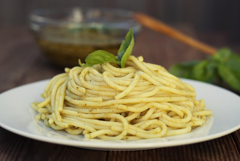 Italian traditional spaghetti with basil pesto pasta with cheese, pine nuts, olive oil, rustic table. Copy space. stock photos
