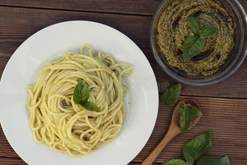 Italian traditional spaghetti with basil pesto pasta with cheese, pine nuts, olive oil, rustic table. Copy space. stock image