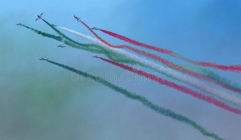 Planes jet of Italian tricolor arrows in acrobatic team during air show, in a spectacular acrobatics royalty free illustration