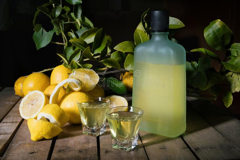 Italian typical digestive limoncello with fresh lemons on a old wooden background, low key royalty free stock photos