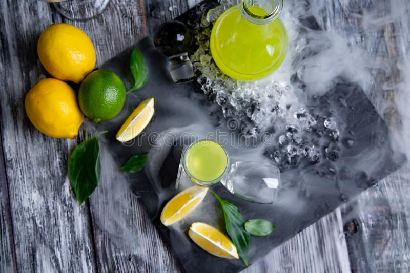 Italian typical digestive limoncello with fresh lemons in smoke, selective focus stock photo