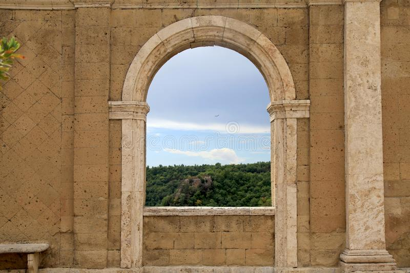 Italian view through the arch window in Sorano, Tuscany, Italy. stock image