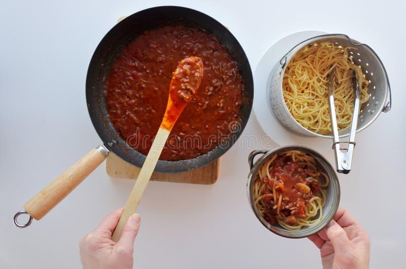 Italian woman cooking homemade Spaghetti Bolognese. POV of Italian woman cooking and serving classic homemade Spaghetti Bolognese meal served in a bowl. Italian royalty free stock image