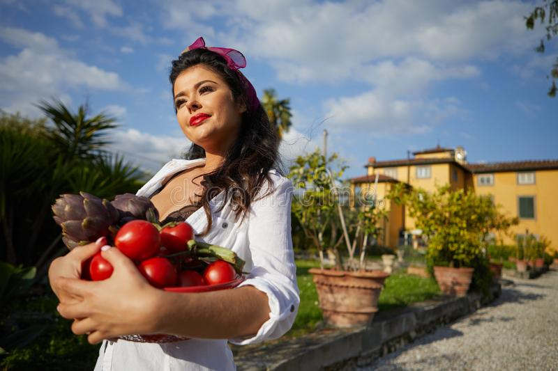 An Italian woman, a housewife, collects vegetables for dinner in a home garden.  royalty free stock photos