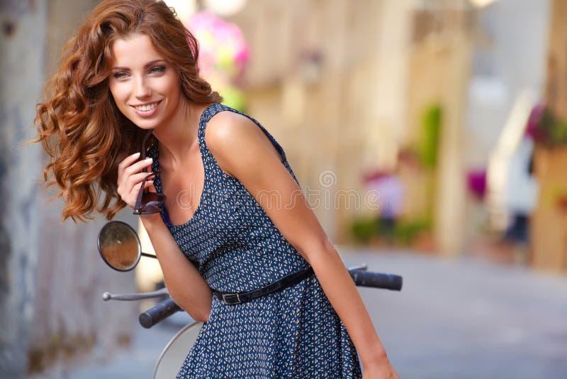 Italian woman sitting on a italian scooter royalty free stock photo