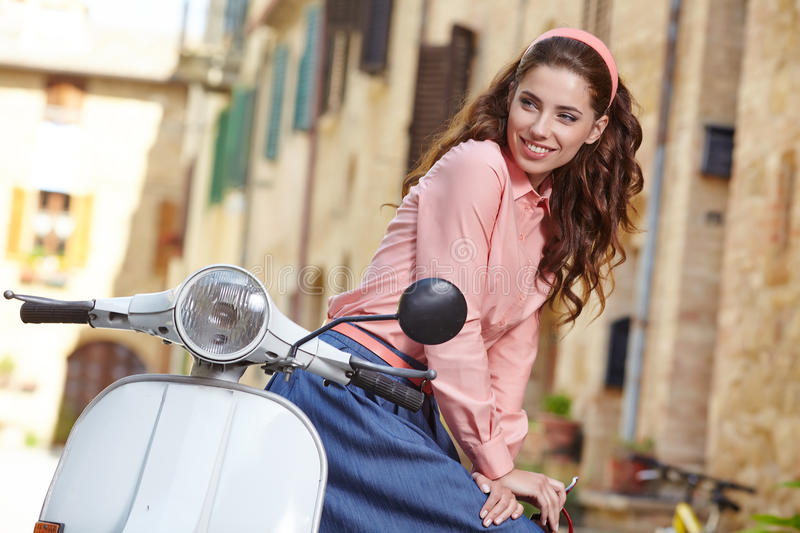 Italian woman sitting on a vintage scooter. stock photo