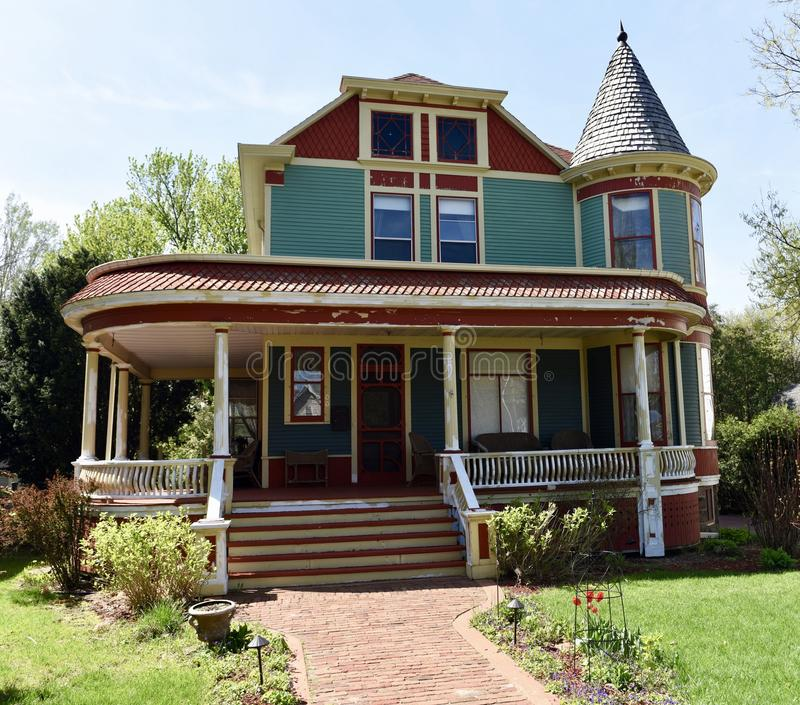 Italianate in Baraboo. This is a Spring picture of a colorful Example if Italianate architecture featuring a corner two story tower and a wraparound porch royalty free stock images