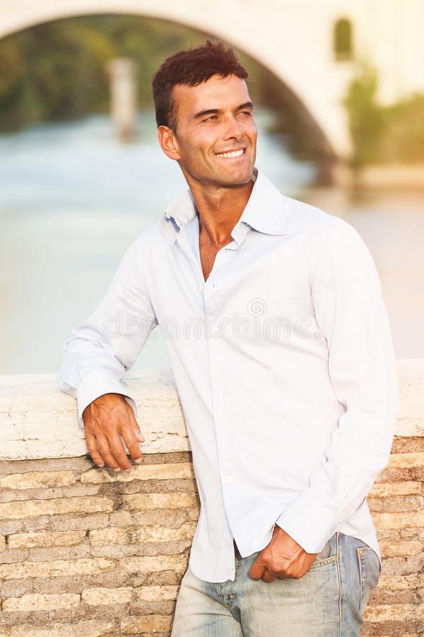 Italiano bello dell'uomo all'aperto a Roma Italia Fiume e ponte del Tevere fotografia stock