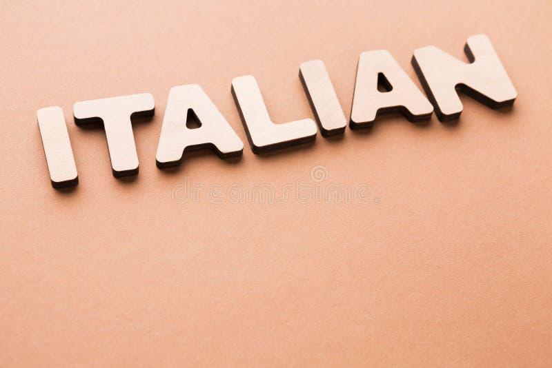 Italiano da palavra no fundo bege fotografia de stock royalty free