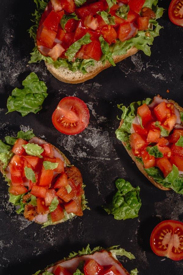 Italiano tradicional Bruschetta com tomates, molho da mussarela, as folhas da salada e o presunto desbastados em um fundo escuro  fotografia de stock royalty free