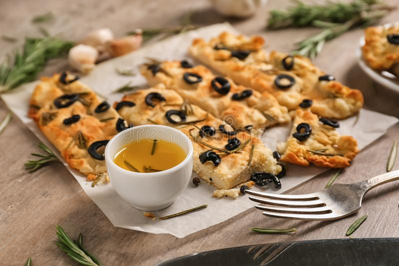 Italiano tradicional Focaccia com alecrins, azeitonas e óleo na tabela foto de stock
