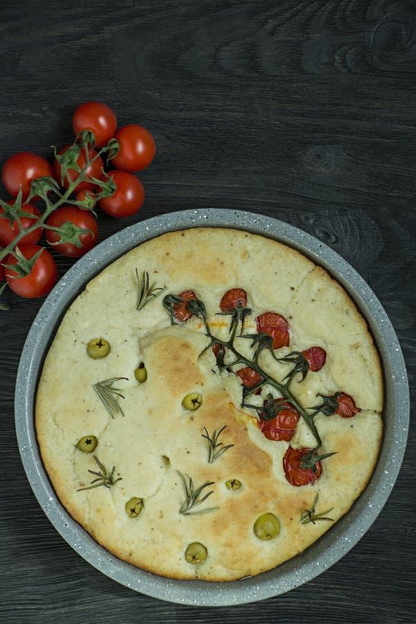 Italiano tradicional Focaccia com tomates, azeitonas e alecrins Focaccia cozido em uma bandeja de cozimento Formul?rio redondo O  imagens de stock royalty free