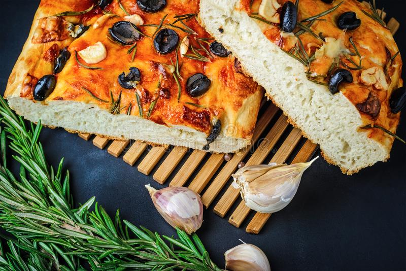 Italiano tradicional Focaccia con las aceitunas, el ajo y el romero, pan hecho en casa imágenes de archivo libres de regalías