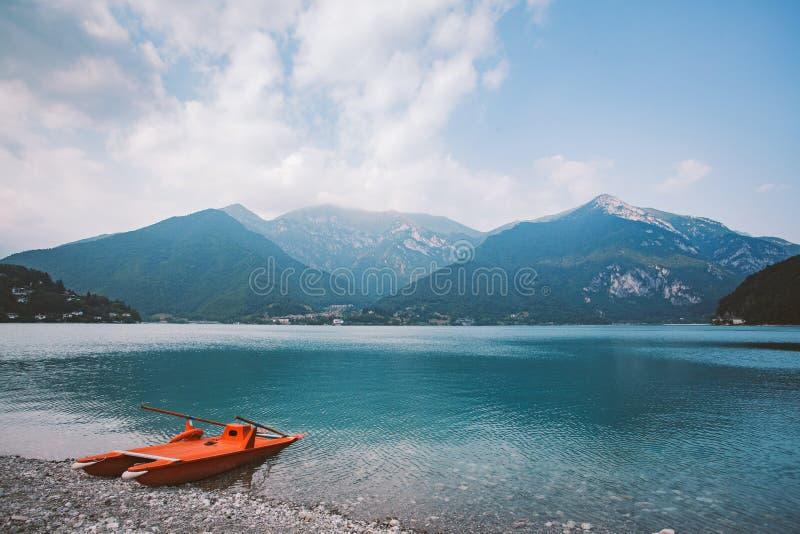 Italien-Ansicht eines Berges lake Lago di Ledro mit einem Strand und einem Rettungsbootkatamaran roter Farbe im Sommer im wolkige stockbilder