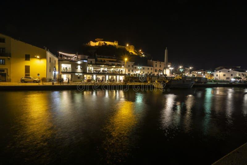 Italien, Tuscany Maremma Castiglione della Pescaia, fyrverkerier över havet, panorama- nattsikt av porten och slotten royaltyfri bild